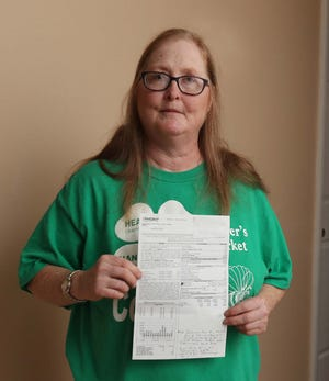 Sharon Burnett holds a bill with a late fee that was added because the U.S. Postal Service delivered it after its due date.