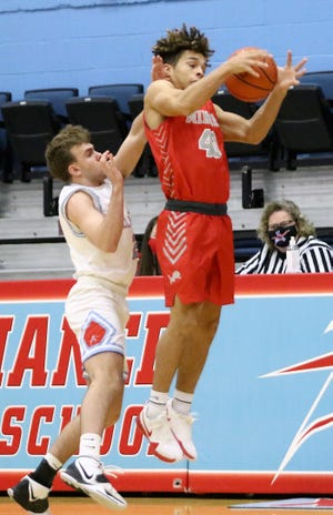 Minerva's Chance Martineau, right, leaps for a pass defended by Alliance's Caden Bates during action at Alliance High School on Tuesday, January 5, 2021.
