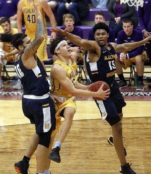 Ashland University's Aaron Thompson goes up for a shot between Alderson Broaddus' Malik Bocook and Troy Cantrell during a game last season.
