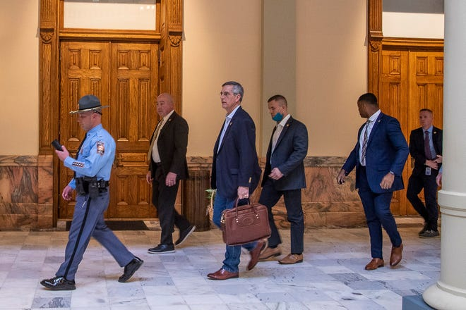Led by a Georgia State Trooper, Georgia Secretary of State Brad Raffensperger, center, exits the Georgia State Capitol building after hearing reports of threats, Wednesday, Jan. 6, 2021, in Atlanta.