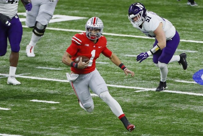 Ohio State Buckeyes quarterback Justin Fields (1) rushes upfield ahead of Northwestern Wildcats linebacker Blake Gallagher (51) during the first quarter of the Big Ten Championship football game at Lucas Oil Stadium in Indianapolis on Saturday, Dec. 19, 2020.