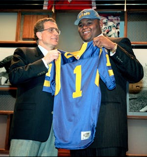 Orlando Pace, right, Ohio State's massive tackle, holds a St. Louis Rams jersey with the help of NFL Commissioner Paul Tagliabue after Pace was chosen by the Rams as the first-round pick in the NFL draft in New York, Saturday, April 19, 1997. (AP Photo/Kevin Larkin )