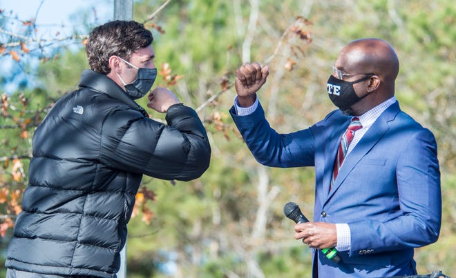 Jon Ossoff (left) and Raphael Warnock exchange elbow bumps during a campaign rally Monday in Augusta, Ga.