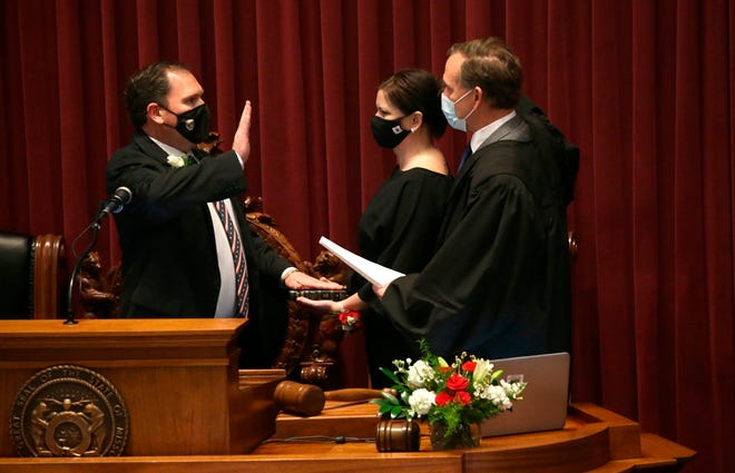State Rep. Rob Vescovo, R-Arnold, places his hand on the bible held by his wife Amanda as he takes the Oath for Speaker of the House on Wednesday.