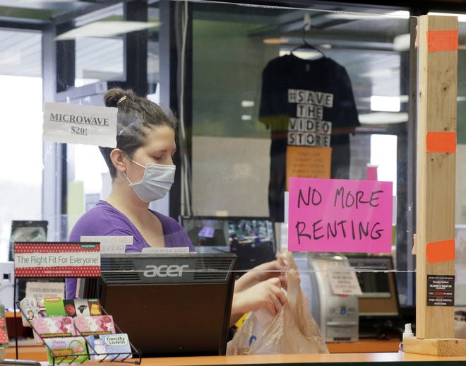 Family Video is closing is remaining locations in Central Ohio, including the store on Dublin-Granville Road on the North side of Columbus, Oh. on Wednesday, January 6, 2021. Store manager Demetra Fotis bags a customer's purchase from behind a plexiglass barrier.