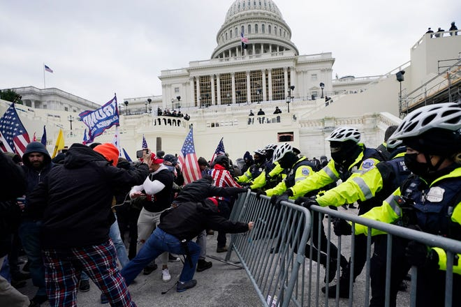 Supporters of President Donald Trump work to break through a police barrier last Wednesday as they stormed the Capitol in Washington.