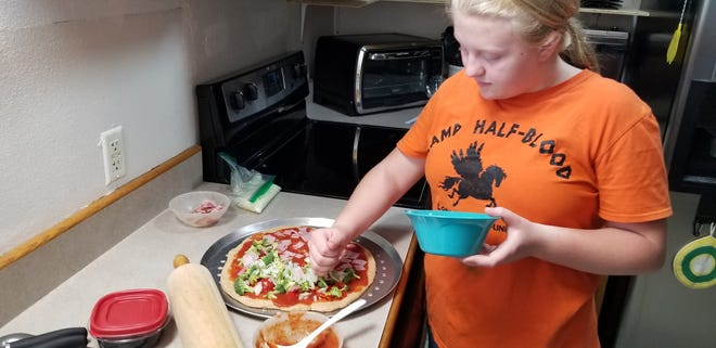 Autumn Patterson, right, creating her own pizza during Grow Your Own Pizza.
