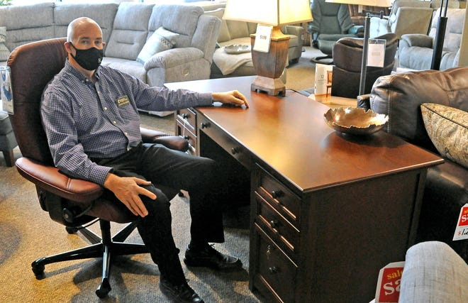 Davis Graham of Runions' Furniture in Orrville sits at one of their desks that could be used for someone's home office druing the pandemic.