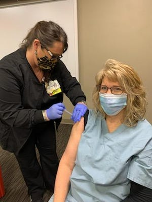 Amanda Strouse administers a Moderna Covid-19 vaccination to Kathy Conn at Pomerene Hospital on Tuesday, where front line staff, such as health care workers received the first round of vaccines.