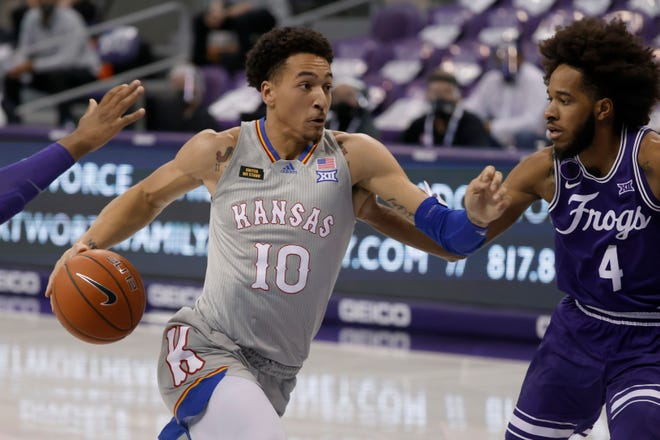 Kansas forward Jalen Wilson (10) drives against TCU guard PJ Fuller (4) during the first half of Tuesday's game in Fort Worth, Texas. Kansas claimed its 11th straight conference road victory with a 93-64 win.