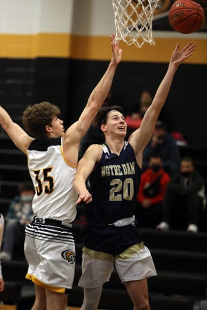 Notre Dame High School's Josh Smith (20) puts up a shot under the basket during the first half of their game against New London High School, Tuesday Jan. 5, 2021 at New London.