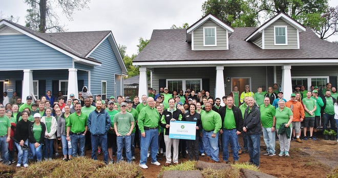 At HabiJax's 2019 Publix Serves Day, CEO Mary Kay O'Rourke (front, center right, holding sign) and volunteers celebrate their work on new Habitat on Rayford Street in Jacksonville. O'Rourke retired last month after serving the nonprofit in some capacity for 23 years.