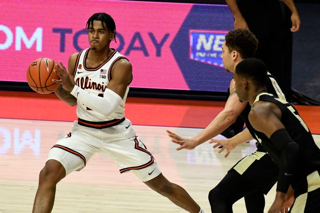 Illinois guard Adam Miller (44) passes the ball as Purdue's guard Brandon Newman (5) and forward Mason Gillis (0) defend in the first half of a game on Saturday, Jan. 2, in Champaign. (AP Photo/Holly Hart)
