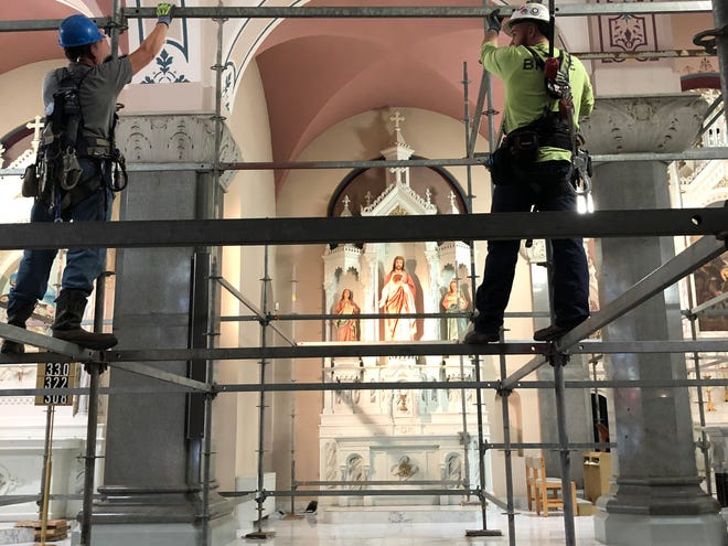 Wichita-based Brace Midwest employees Michael Oliveras, left, and Todd Mellinger, right, on Tuesday install scaffolding at The Basilica of St. Fidelis in Victoria in preparation for painting the interior.