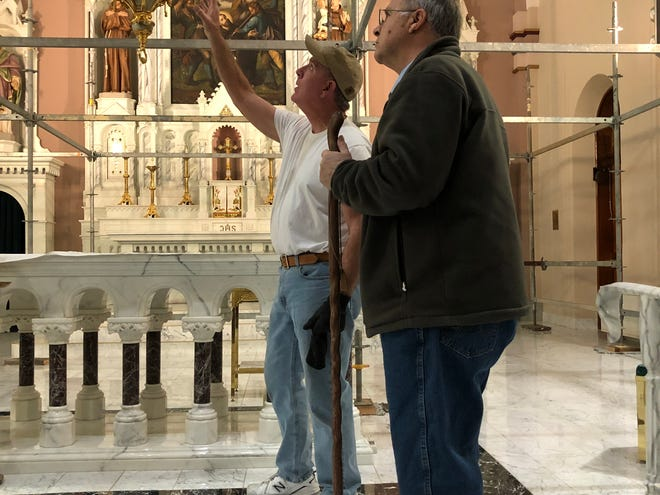 St. Fidelis parishioner Harland Rupp, right, on Tuesday discusses the interior paint for St. Fidelis with contractor Tim Linenberger, left, owner of Tim Linenberger Painting & Decoration Inc. of Salina.