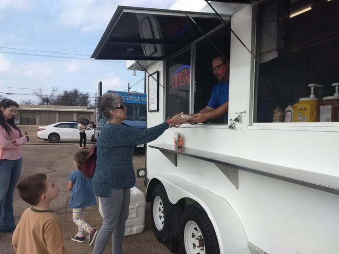 Brad Wells serves a hot dog to Joyce Ashley at the grand opening of Denison's new food truck park in 2018. The city approved a series of updates to its ordinance regard food trucks on Monday.
