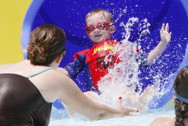 Tommy Williams, 3, is caught by his mom Lisa as he shoots out of the slide at the Salt City Splash in this April 2013 file photo.