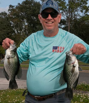Glen Smith of Lakeland shows off two good size specks of a near limit he caught while fishing at Lake Hunter this past weekend.