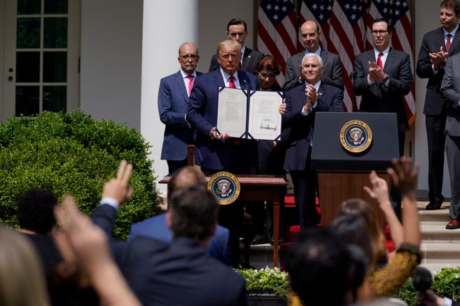 President Donald Trump poses for a photo after signing the Paycheck Protection Program Flexibility Act during a news conference in the Rose Garden of the White House in Washington on June 5, 2020. [AP File Photo/Evan Vucci]