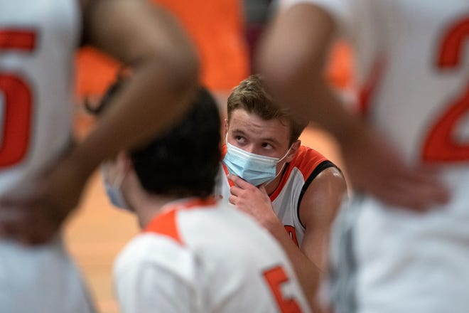 Wayland senior Luke Tacelli listens to Wayland head coach Dennis Doherty during a mask break in between quarters of the season-opening game against Weston at Wayland High School, Jan. 5, 2021. The Warriors defeated the Wildcats, 51-37.