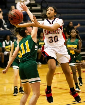 Vanguard's Donita Buie goes in for a layup against Forest's Delana Neal in the first half. The Vanguard Knights defeated the Forest Wildcats 53-30 Tuesday night.