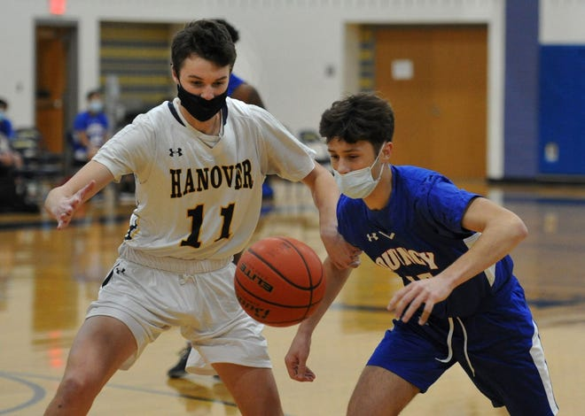Hanover's Jake Peterson, left, and Quincy's Will Cook race for a rebound during boys basketball action at Hanover High School, Tuesday, Jan. 5, 2021.