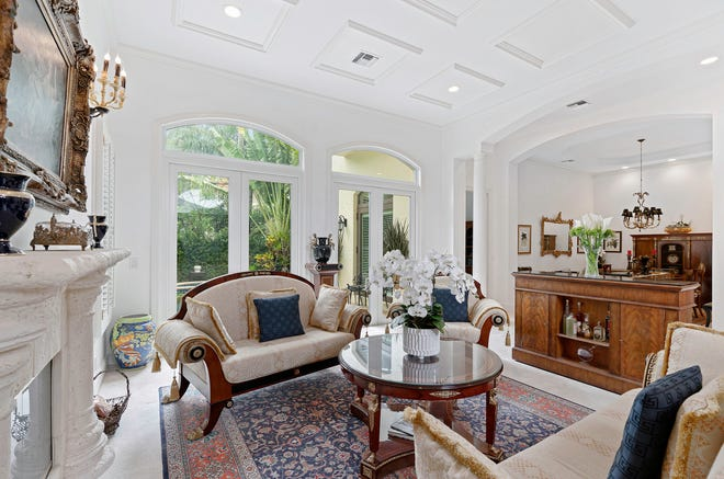 With a fireplace and French doors opening onto the pool area, the living room of a North End townhouse has a tall archway that separates it from the dining room. The four-bedroom residence at 255 Seminole Avenue is listed at $3.5 million.