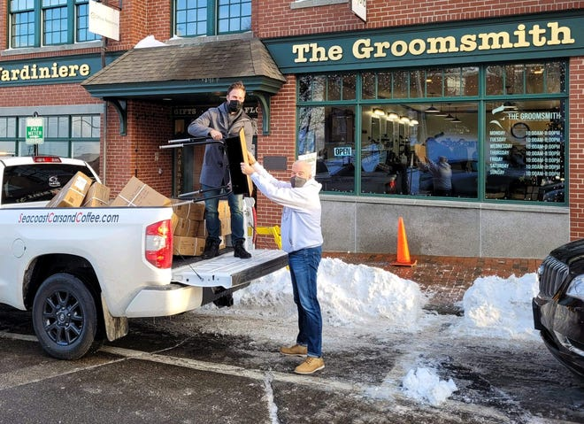 The Groomsmith barbershop founder and owner Reed Maerder unloads a school desk from a pickup truck and hands it to Chase Home for Children ambassador Bill McDonald in December 2020. Maerder and his staff set up a fundraiser that raised money for school desks donated to each of the 15 youth living in Chase Home for Children's residential program, as well as raised an additional $1,400 for other needs.