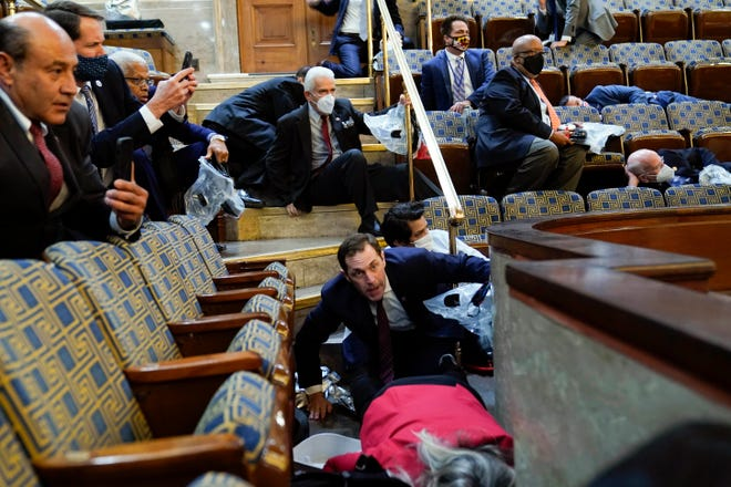 People shelter in the House gallery as protesters try to break into the House Chamber at the U.S. Capitol on Wednesday, in Washington. ANDREW HARNIK / Associated Press