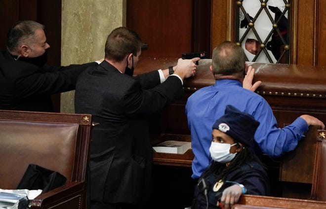 Police with guns drawn watch as protesters try to break into the House Chamber at the U.S. Capitol on Wednesday, in Washington. J.SCOTT APPLEWHITE /Associated Press