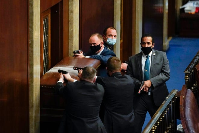 U.S. Capitol Police with guns drawn stand near a barricaded door as protesters try to break into the House Chamber at the U.S. Capitol on Wednesday, in Washington. ANDREW HARNIK / Associated Press