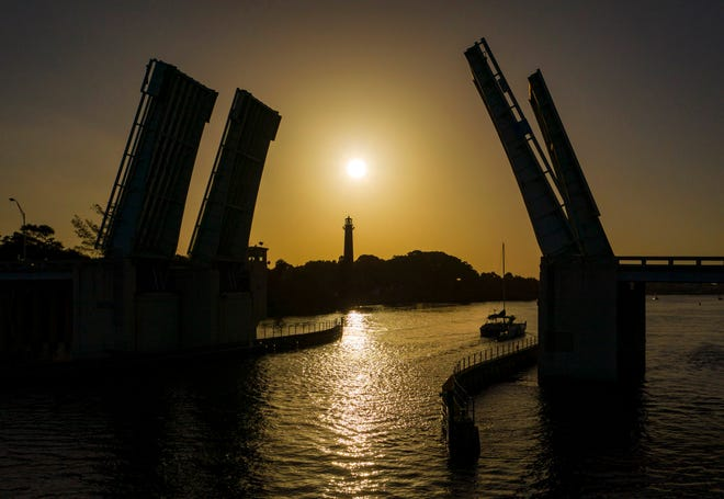 A boat passes under the U.S. 1 bridge as the sun rises in a hazy sky from Saharan dust in Jupiter, Florida on July 1, 2020.