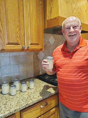 Pratt retiree Darrell Shumway is all smiles as he displays the six jars of horseradish, he recently put up from his 2020 garden harvest.