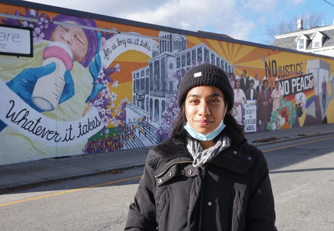 Artist Joyce Kutty stands in front of the mural honoring health-care workers that she and Wes Sanders have nearly completed on the Providence building occupied by the Service Employees International Union District 1199.