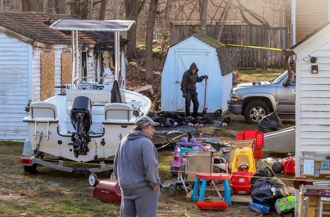 Workers clean up outside the house that caught fire at 1846 New London Turnpike. [The Providence Journal / David DelPoio]