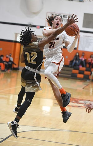 Jayden Ballard of Massillon goes to the hoop in the first half drawing the foul from Demond Carpenter of St. Thomas Aquinas.
