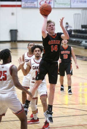 Zack Oddo (14) of Green puts up a floater in the lane as James McCollough Jr. (25) of McKinley moves in on the play during their game at McKinley on Tuesday, Jan. 5, 2021.