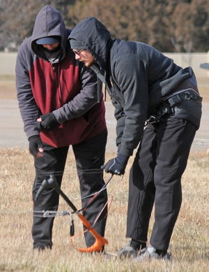 Joel Kerns, left, gives instructions to his son Gage Kerns on how to fly his 6-meter foil kite at the Berkley Family Recreational Area, formerly East Crawford Recreation Area, in Salina on Wednesday. Joel Kerns used the smallest foil kite, which works well for beginners and high winds. The largest foil kite Kerns has is 20 meters.