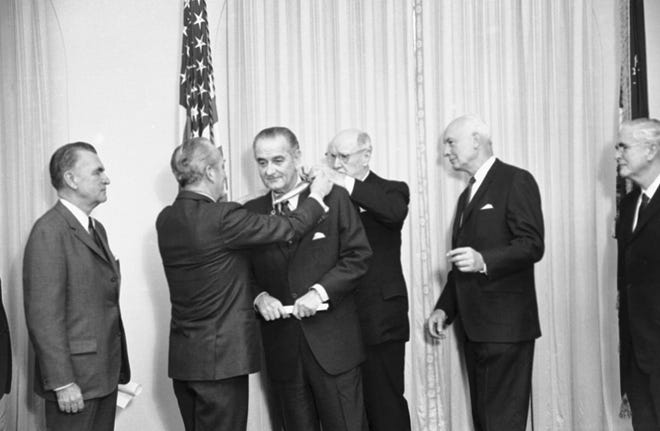 "President Lyndon Johnson is presented a gold medal at a brief White House ceremony by the Pan American Society on Jan. 9, 1969. Placing the medal around the president's neck is Robert M. Reininger, president of he Society, left, with an assist from former Postmaster General James A. Farley. Johnson told the group that after retirement he will continue to maintain a ""deep interest in all that is calculated to advance Latin American benefits."""