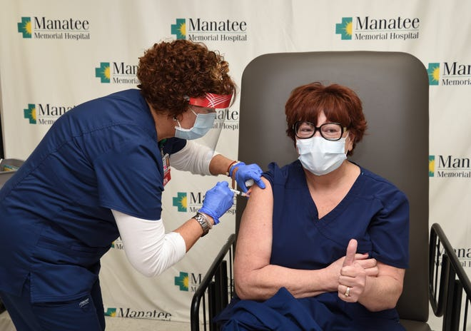 In this undated photo, a Manatee Memorial Hospital worker receives the coronavirus vaccine.