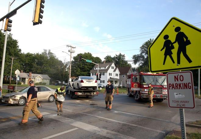 Springfield firefighters help to clear the scene of a two car accident at the intersection of MacArthur Boulevard and Lawrence Avenue, Monday, August 31, 2020, in Springfield, Ill. [Justin L. Fowler/The State Journal-Register]