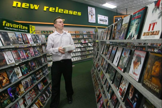 A store manager at Family Video's 1614 S. MacArthur Blvd. location, places DVDs back on the store's shelves in 2014.