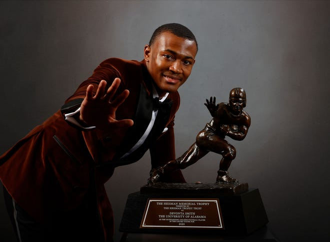 In a photo provided by the Heisman Trophy Trust, Alabama wide receiver DeVonta Smith poses for a photo after winning the Heisman Trophy, Tuesday, Jan. 5, 2021, in Tuscaloosa, Ala. (Kent Gidley/Heisman Trophy Trust via AP)