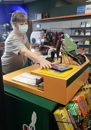 Family Video Manager Kimma McIntyre rings up a sale during the first day of liquidation of the video store's inventory. The store's parent company, Highland Ventures, announced the closing of the itss remaining 250 stores Tuesday.