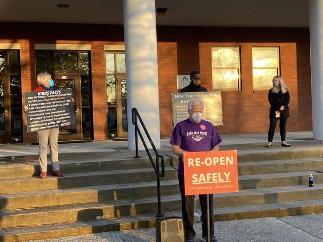 Members of the New Hanover County Association of Educators speaking outside the New Hanover Board of Education building before Tuesday's meeting.