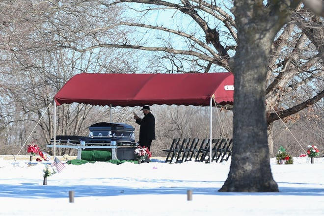 A man stands by a casket following a ceremony Monday afternoon at Memorial Cemetery in Topeka.