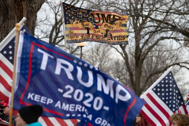 Flags in support of President Trump fly above protesters during a rally at the Statehouse on Jan. 6. It is unclear whether similar protests will occur on Inauguration Day. (Evert Nelson/The Capital-Journal)