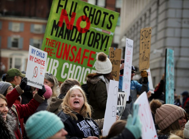Demonstrators rally outside the Massachusetts State House, protesting Gov. Charlie Baker's order for mandatory influenza vaccinations for students Wednesday in Boston.