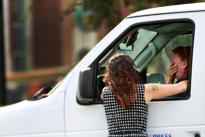 A witness wipes away tears at the scene where 20-year-old University of Florida student Abigail Dougherty was killed by a garbage truck on West University Avenue in 2014.
