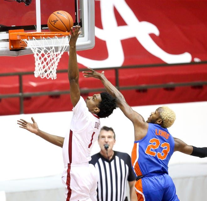 Alabama forward Herb Jones drives to the basket Tuesday against Florida guard Scottie Lewis (23) at Coleman Coliseum in Tuscaloosa, Ala.